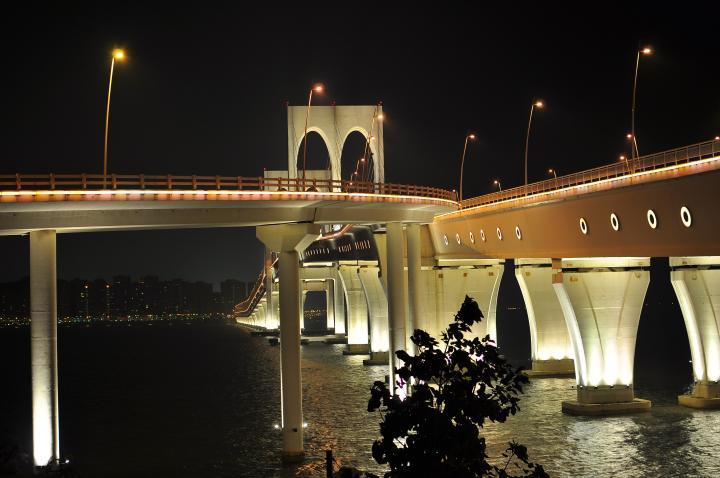"""西湾大桥 西湾大桥是连接澳门半岛和氹仔岛的第三座大桥,于2002年10月8日动工兴建,主桥于2004年6月28日合龙。西湾大桥北起澳门半岛融和门,南至氹仔码头,采用""""竖琴斜拉式""""设计,两个主桥趸之间跨度达180米。该桥总长2200米,分上下两层:上层为双向6车道,下层箱式结构,双向4车道行车,可以在8级台风时保证正常交通,桥内还预留了铺设轻型铁轨的空间。"""
