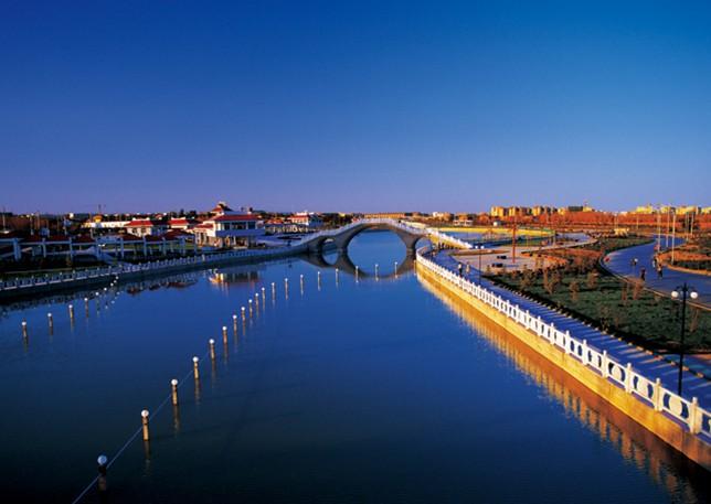 克拉玛依河 克拉玛依河又名穿城河,克拉玛依市区境内,交通极便利。克拉玛依河从城区东北入境,在城中曲折穿越后城区西南进入西郊水库,全长8.51千米,河宽约15米。友谊桥是进入克拉玛依市的门户,桥主体魏斜拉桥,风格独特,美观精巧。全桥采用高杆灯及彩球射灯照明,塔柱安装霓虹软管装饰灯,斜拉索安设跑灯带,成为克拉玛依河上一重要的景点。其余四座交通桥为准葛尔桥,昆仑桥,胜利桥,和西环桥。15座人行桥和非机动桥分布在不同的河段。克拉玛依河两岸宽展的绿化带,占地面积15.
